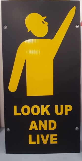 Reflective pointing man 'look up and live' sign